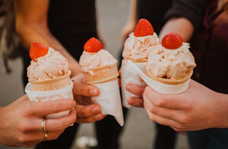 people holding strawberry ice cream cones