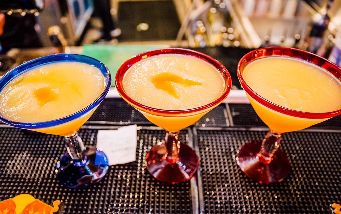 Three giant frozen margaritas on a bar