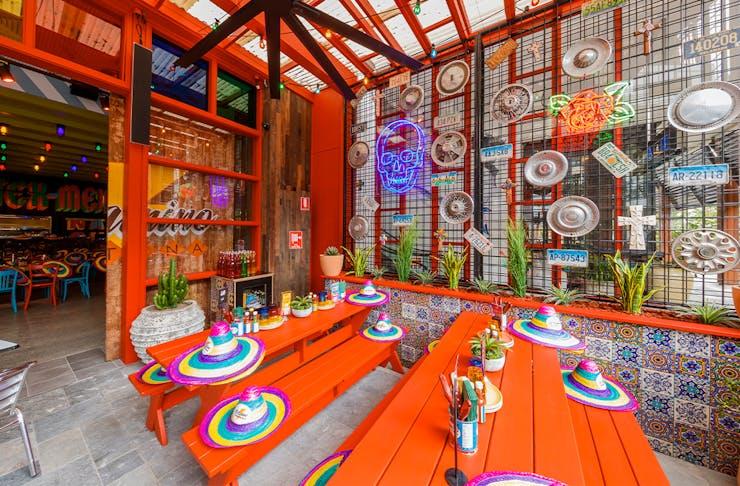 Bright, colourful picnic tables and hub cap adorned walls at El Camino in Chermside