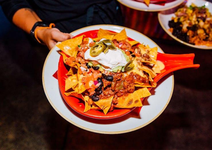 Waiter holding a bowl of nachos
