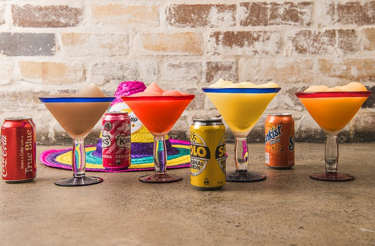 a row of frozen margaritas with soft drink cans alongside