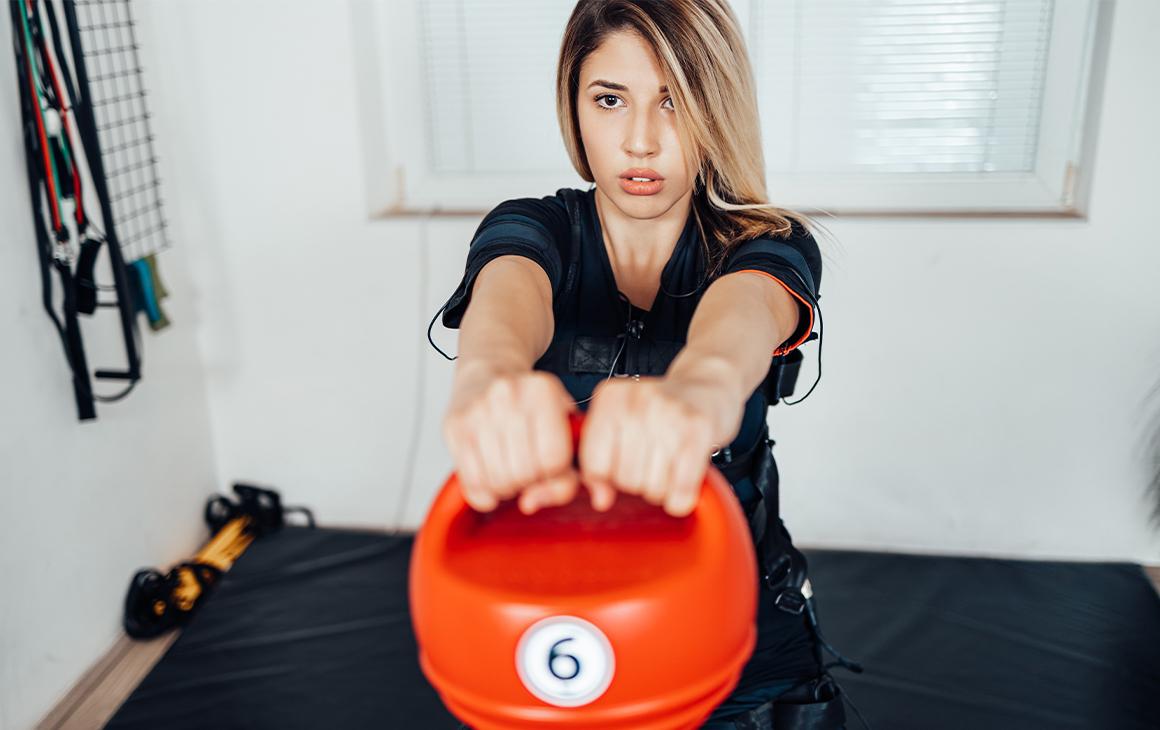 a woman in a vest swinging a kettle bell