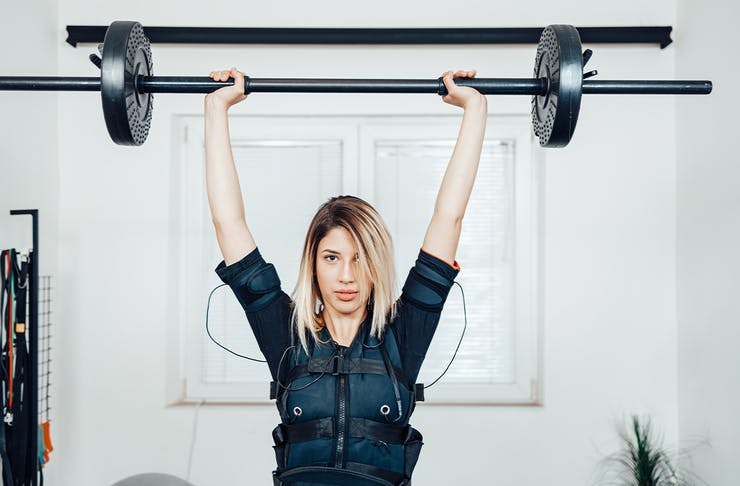woman in an EMS training vest lifting a barbell
