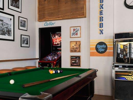 A pool table, pinball machine and juke box at a pub.