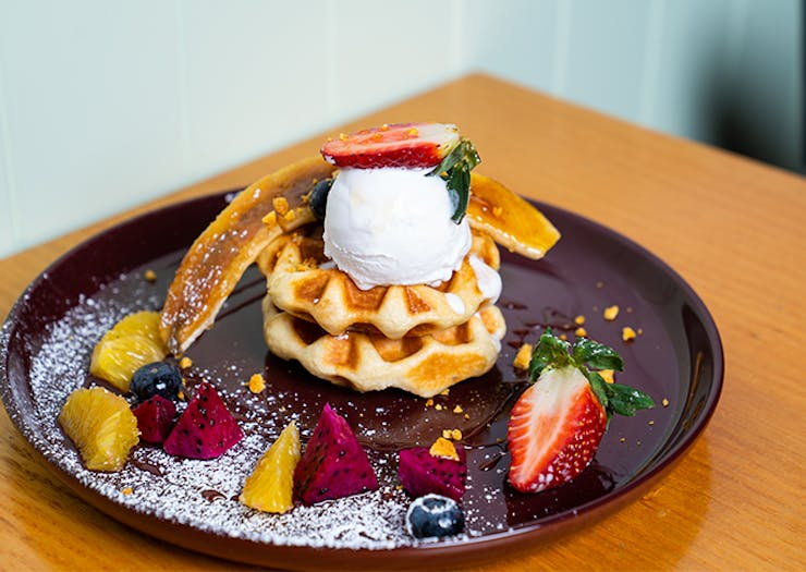 a plate of waffles topped with fruit