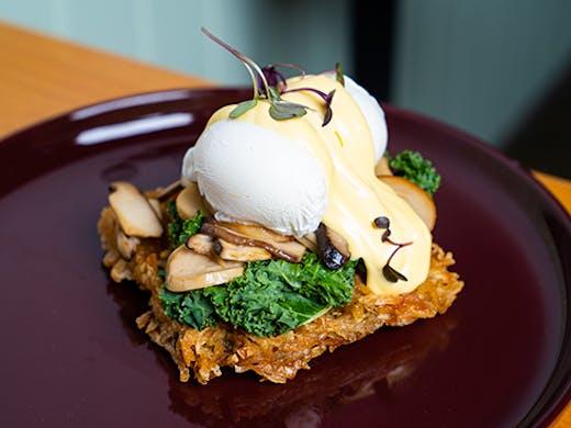 a potato waffle topped with eggs, kale and mushroom
