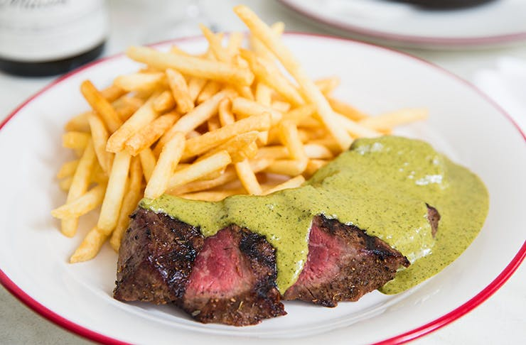 A steak from Entrecôte covered in their herb and butter sauce.