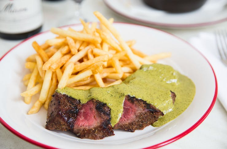 Entrecote's famous steak with secret green sauce served on a plate with frites.