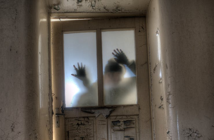 A man's shadow on a locked door with hands on the glass.
