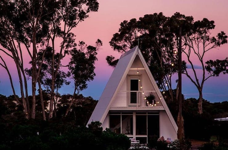 a small white cottage set amongst treets at sunset