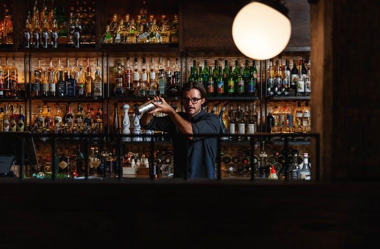 A barman at the bar shaking a cocktail at Esteban Sydney.