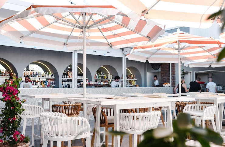 a bar area with striped umbrellas above tables