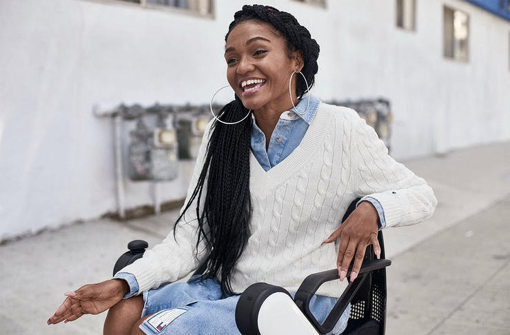 A girl in a wheelchair looks very happy in her cool new Tommy Hilfiger adaptive threads.