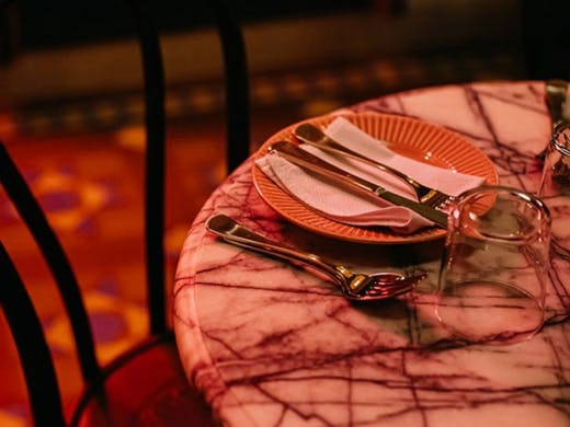 A marble table set with pink plate under a pink neon sign.