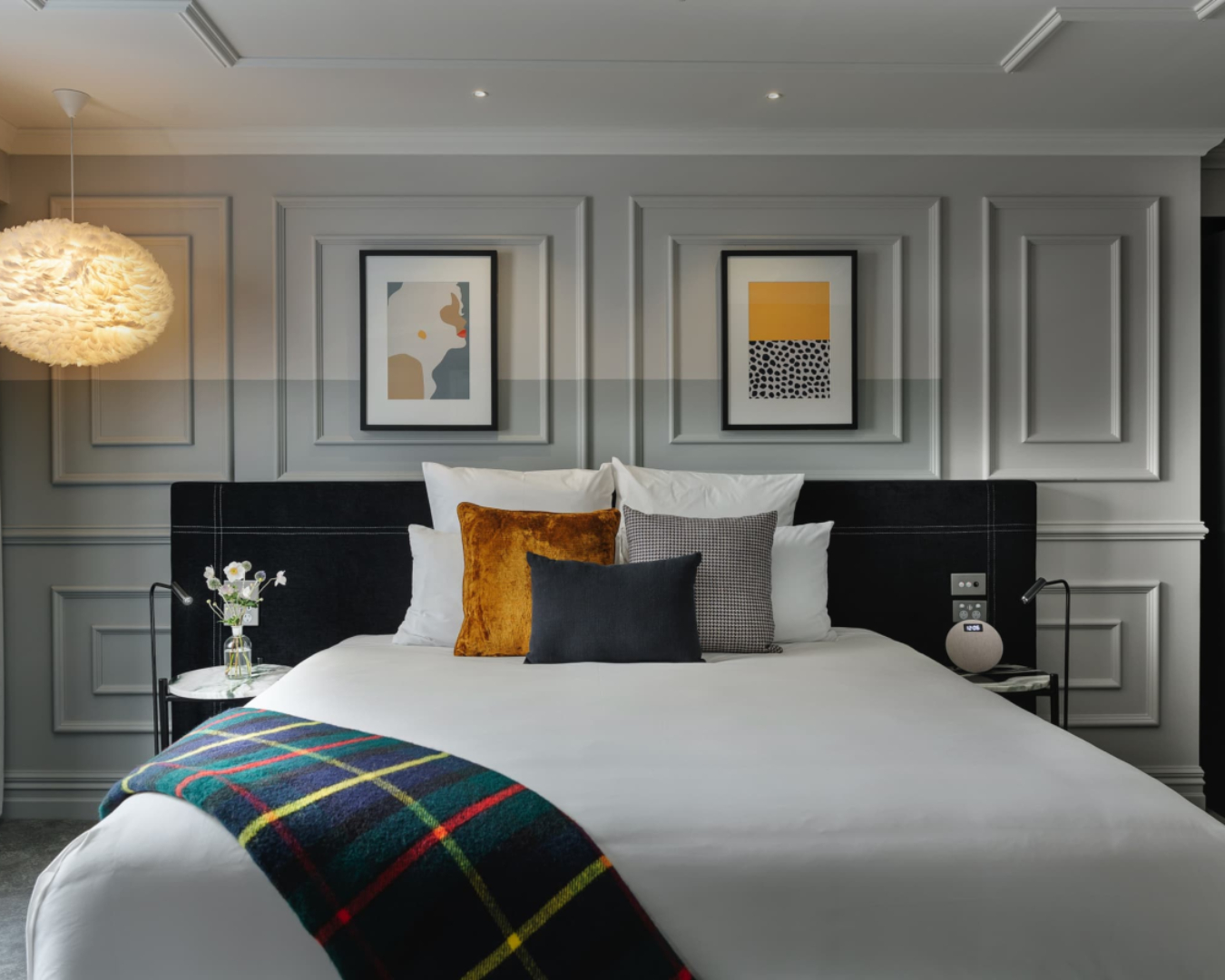 An elegant guest suite at the Fable hotel in Dunedin, featuring a plush bed with a tartan throw