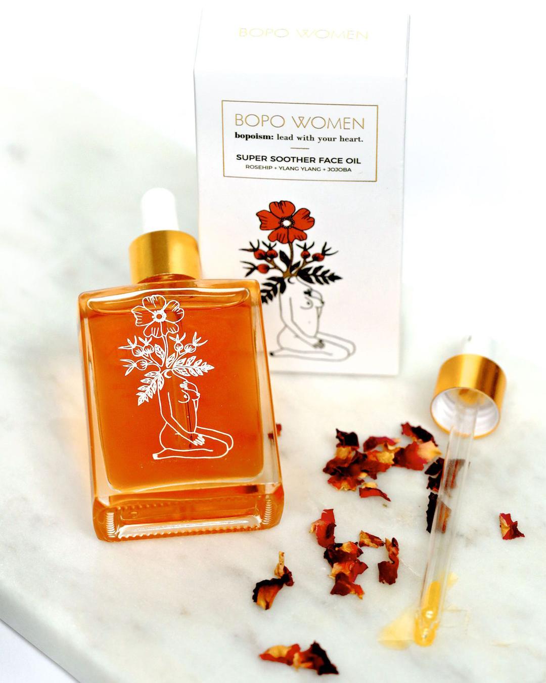 An orange facial oil in a rectangular glass bottle set amongst rose petals