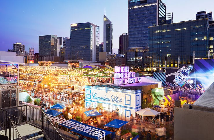 a large outdoor event space lit up in front of the Perth city skyline