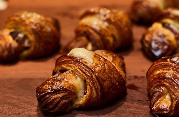 A cheese-filled croissant on a wooden table.
