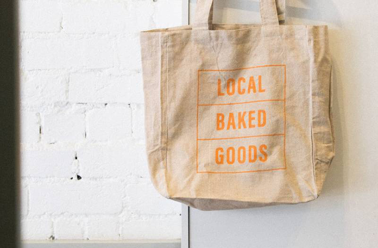 A natural-coloured tote bag hanging from a door with a print on the front that reads