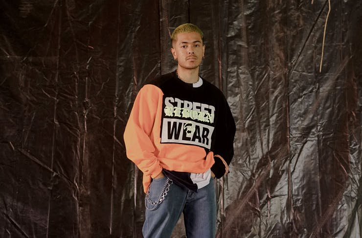 A man wearing an orange and black jumper from Melbourne-based social enterprise and fashion label HoMie. The jumper is a part of HoMie's repurposed fashion collection.