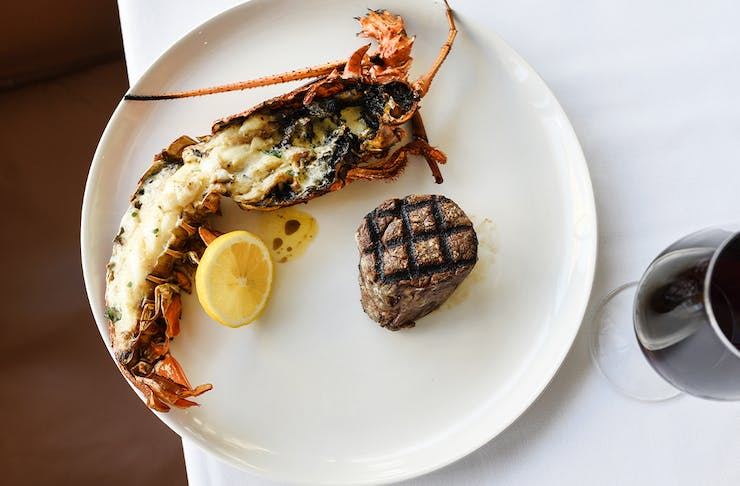 a steak and a half rock lobster on a plate with a glass of wine