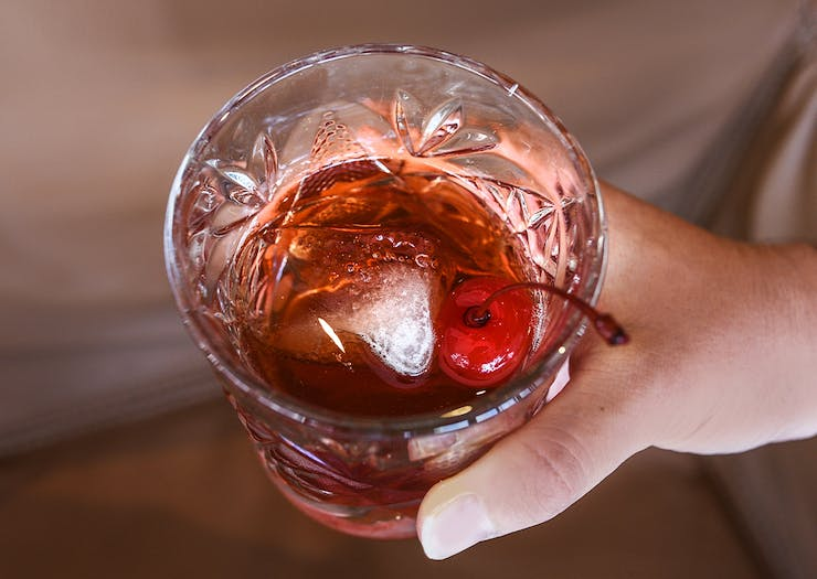 a hand holding a cocktail in a short glass