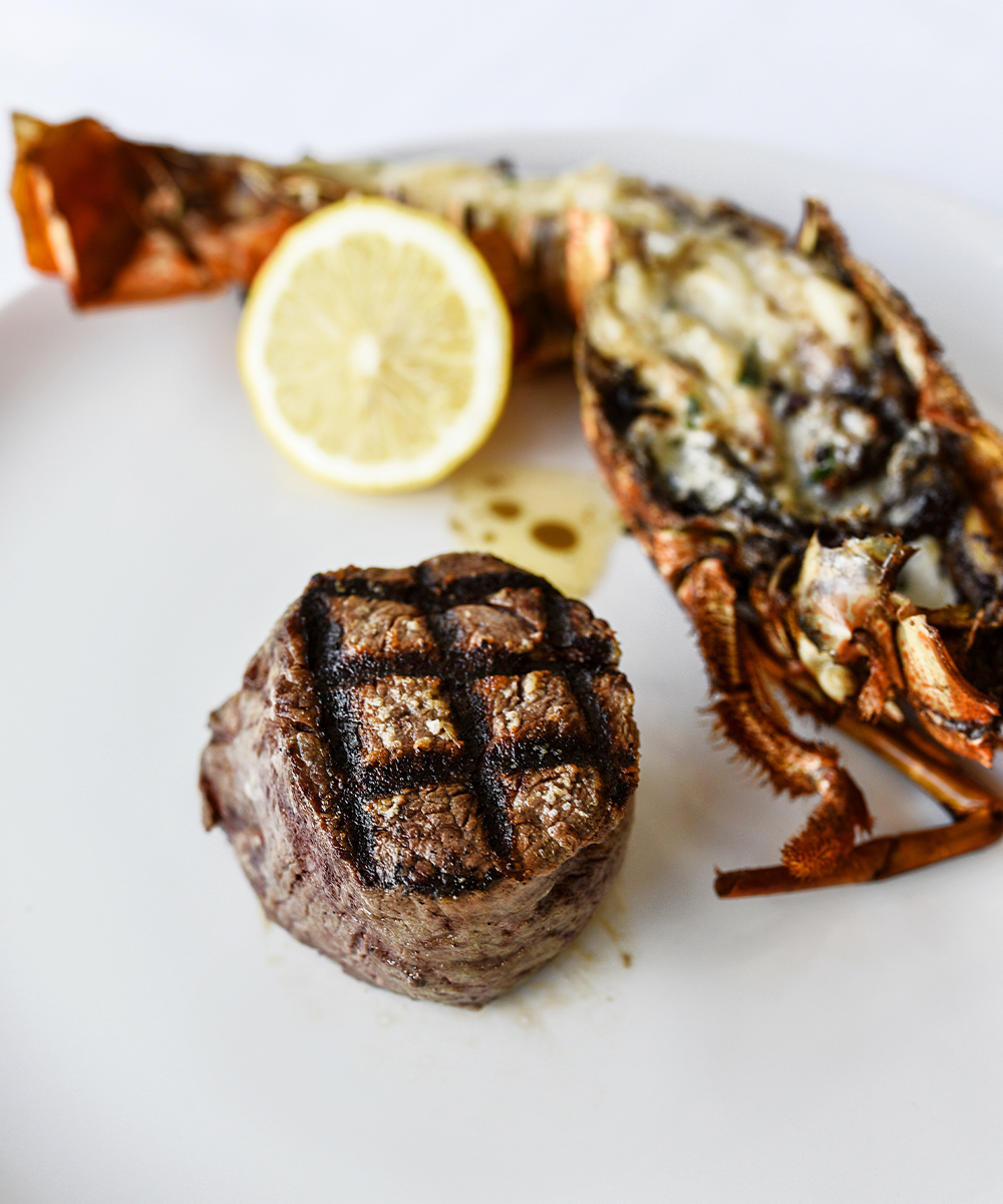 a steak and half a lobster on a plate