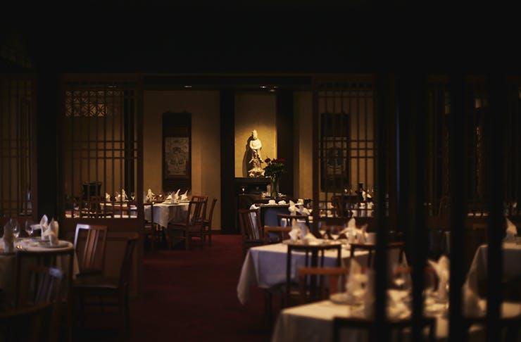 The moody, darkly lit interior of Flower Drum restaurant.
