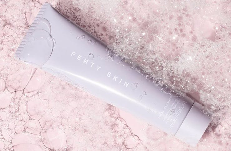 A tube of Fenty Skin moisterizer on a bubble covered pink surface