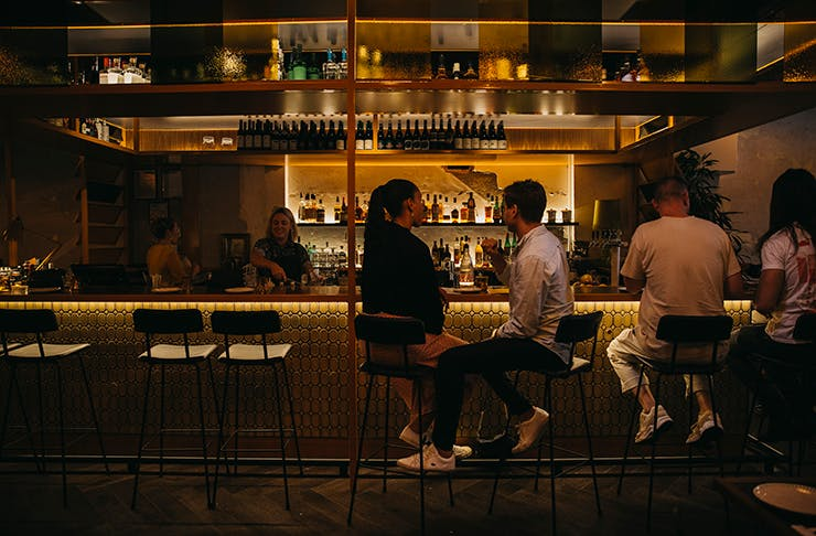 A dimly lit restaurant with two people dining together under red light.