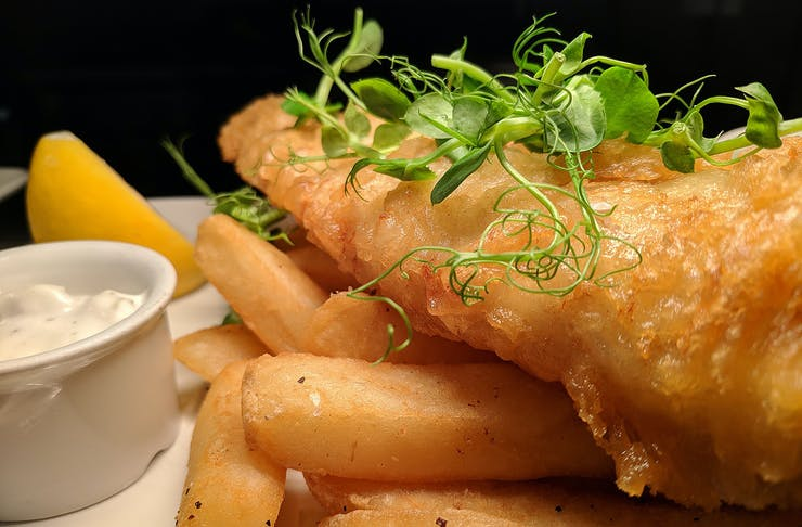 Fish and chips sit on a plate with a wedge of lemon and tartare sauce on the side.