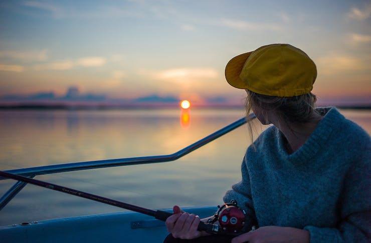 A woman looks at the horizon as she fishes off a boat.