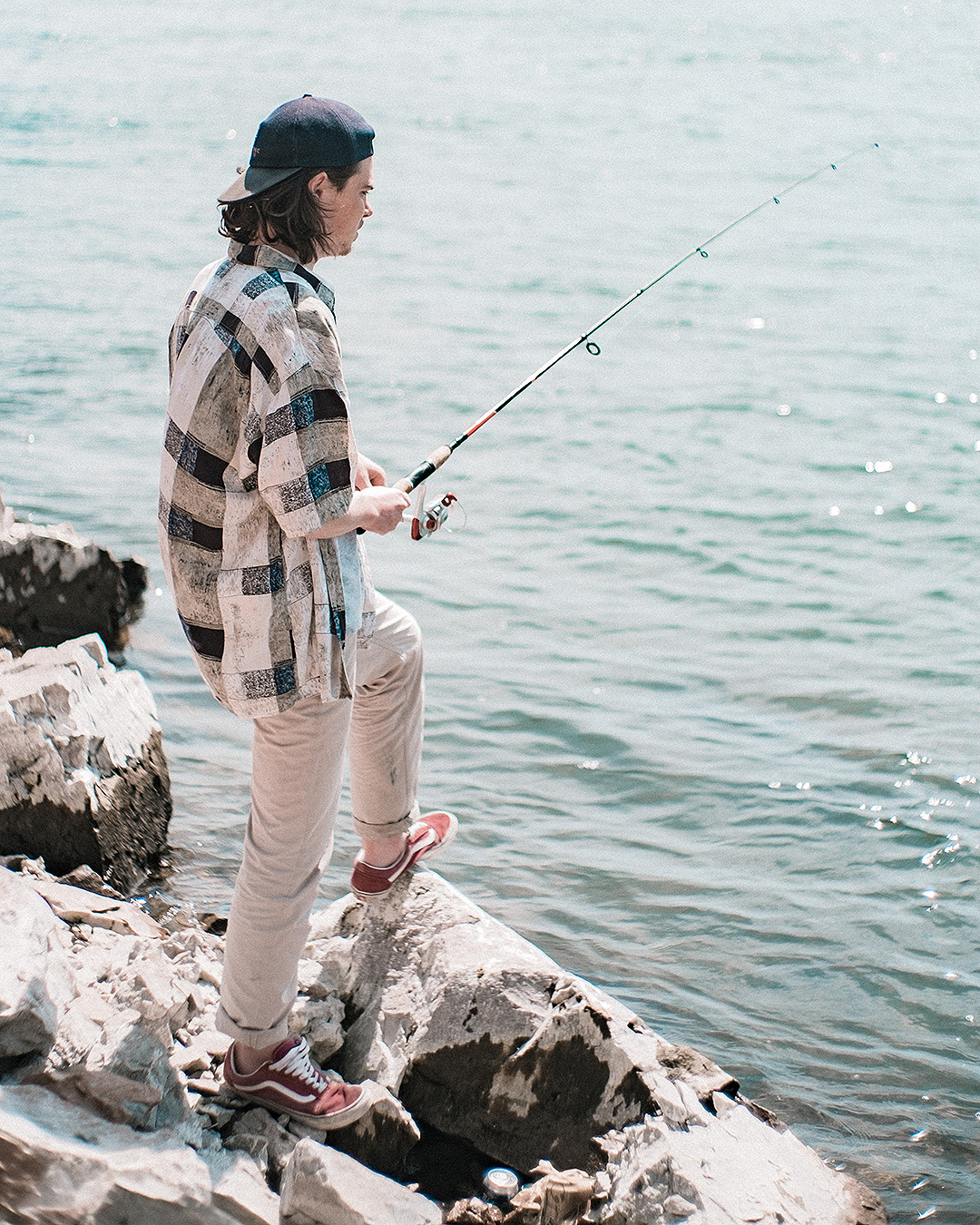A guy fishes off the rocks.