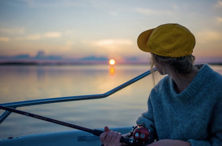 A girl holds a fishing rod