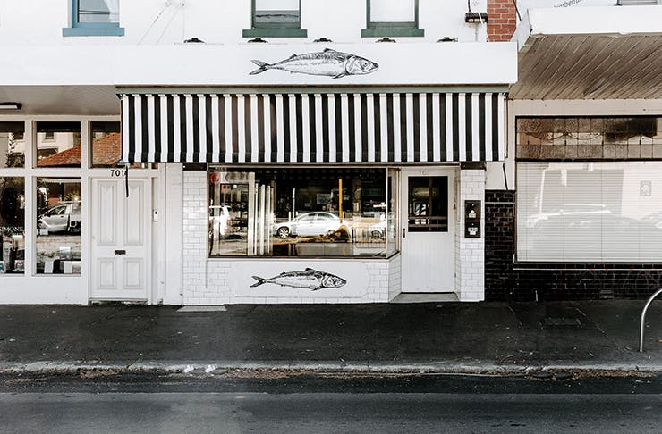 The white and black exterior of a fishmonger.