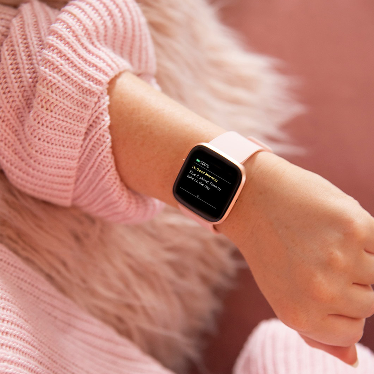 a pink fitbit on someone's wrist