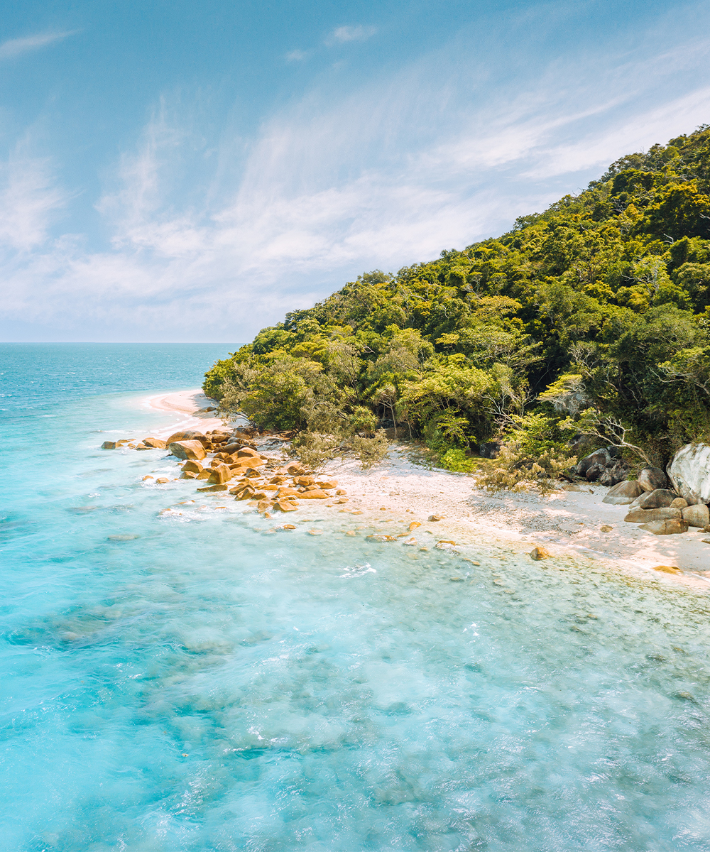 fitzroy island beach with rocks and blue water