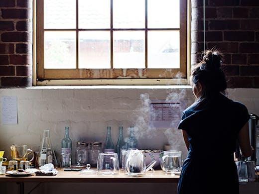 A woman making tea in a warehouse.