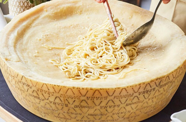 a giant cheese wheel with pasta in it