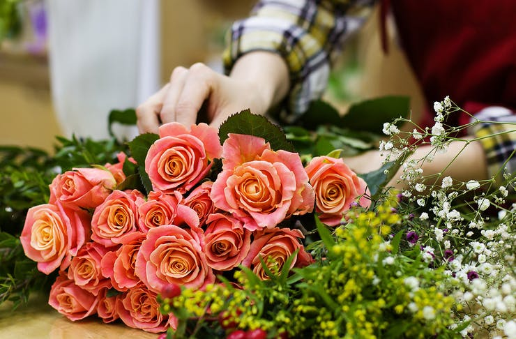 A woman carefully arranges a bunch of colourful flowers.