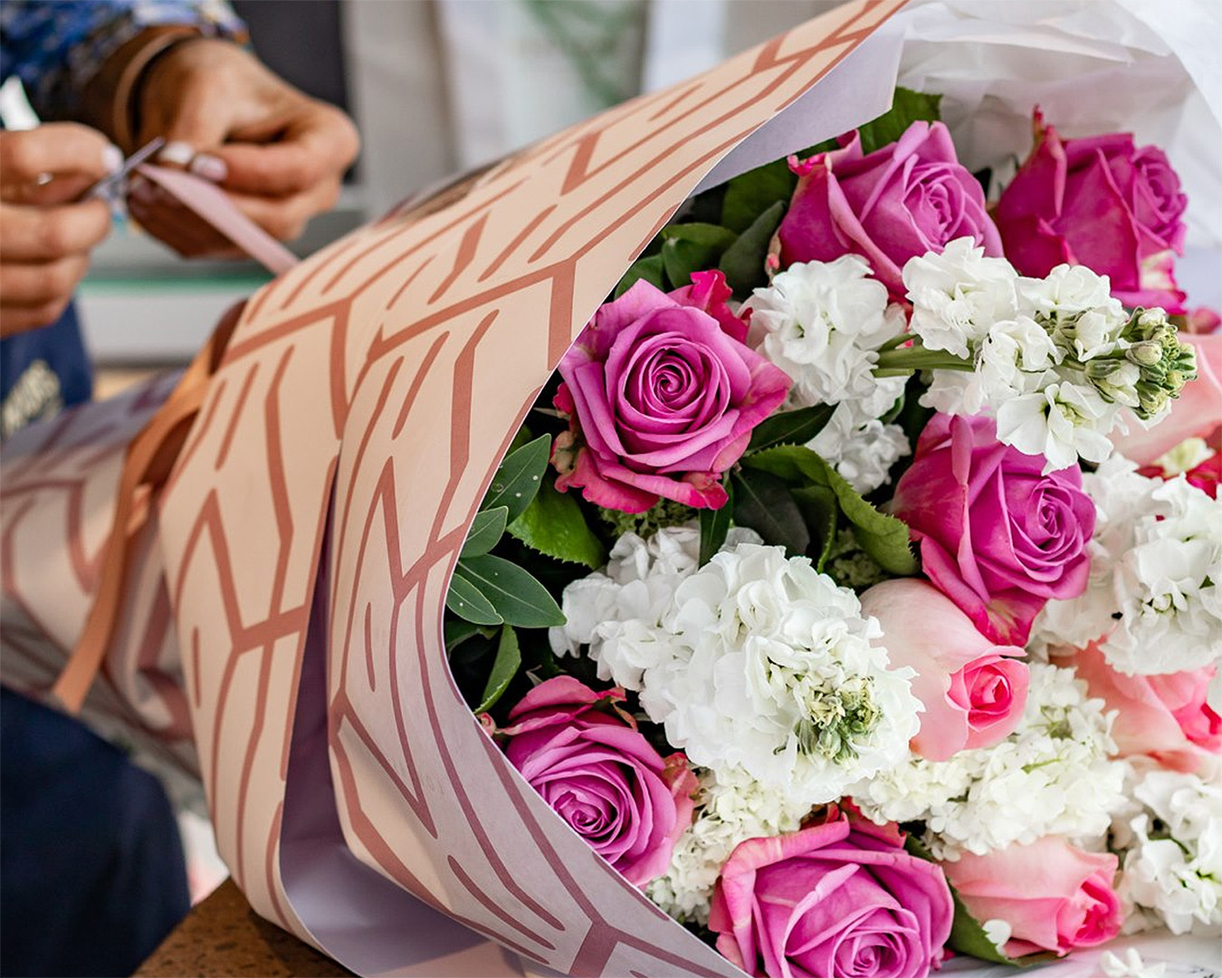 Someone adds the finishing touches to a lovely bouquet from Flowers after hours.