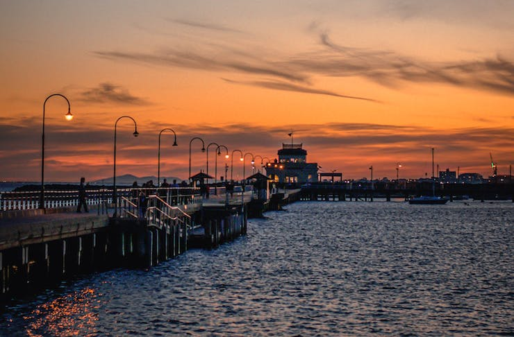 A St Kilda jetty soaked in orange hues at sunset.