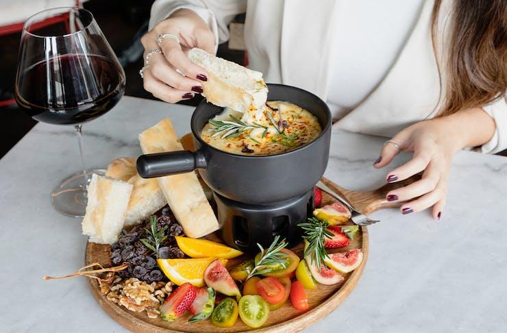 a person dipping focaccia into cheese fondue