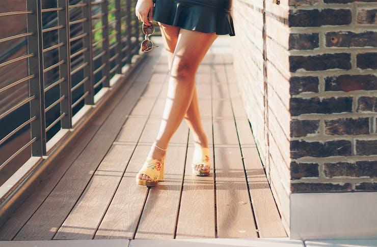 A woman's legs, standing on a verandah