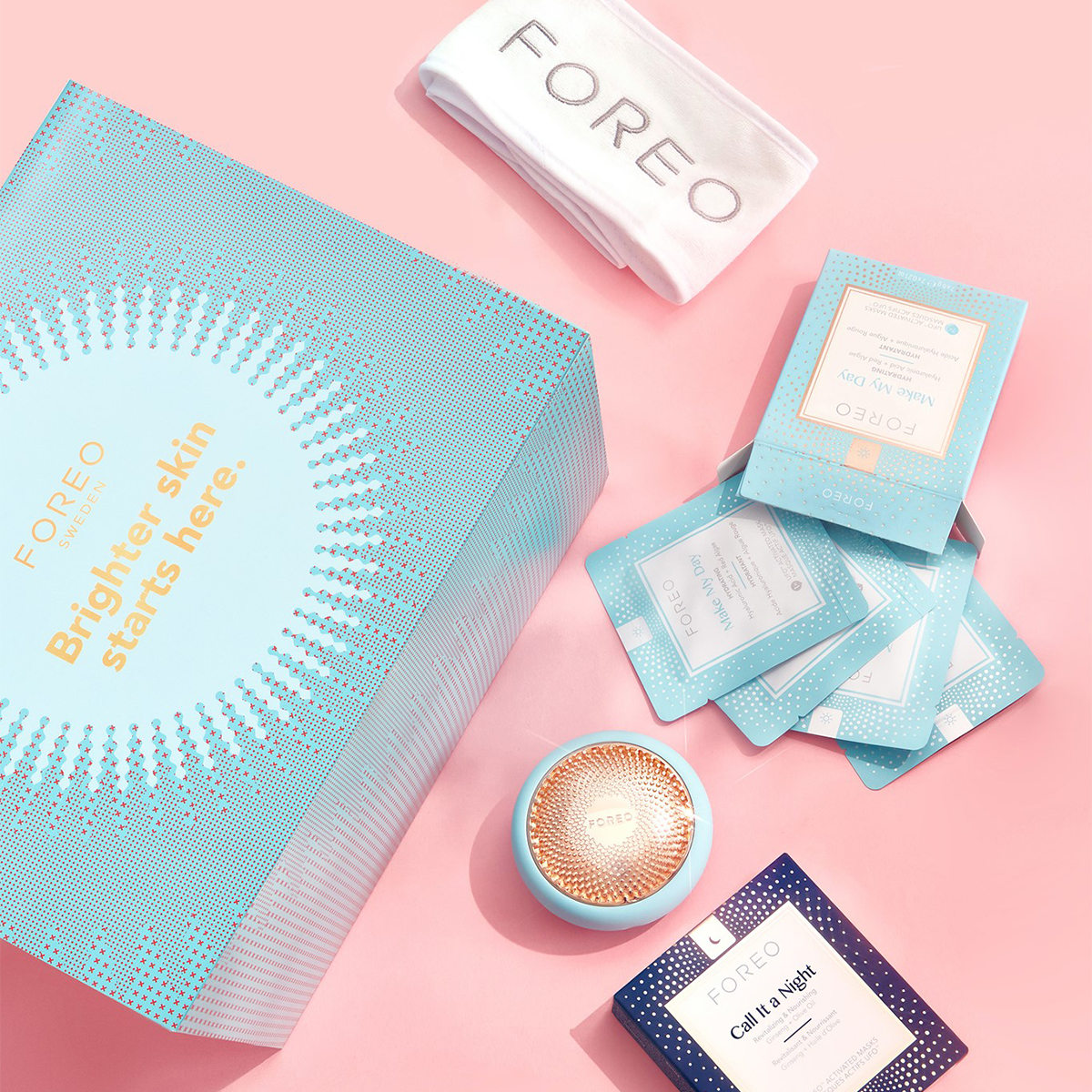 a small foreo light device and several different sheet mask packets