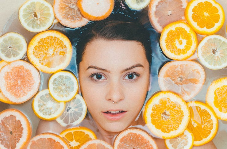 woman's face in bath surrounded by orange slices
