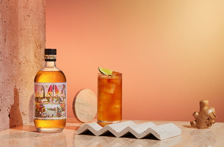 A bottle of Four Pillars Gin on a warm-hued set with ginger placed sporadically in the shot.