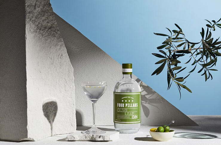 A stylised photo of Four Pillars Olive Leaf gin, featuring a martini and a bowl of olives.