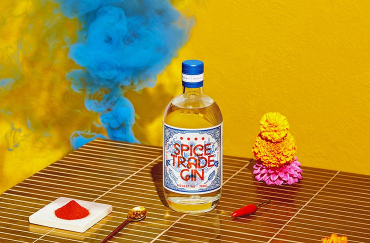 A bottle of colourful gin next to spices and blue smoke.