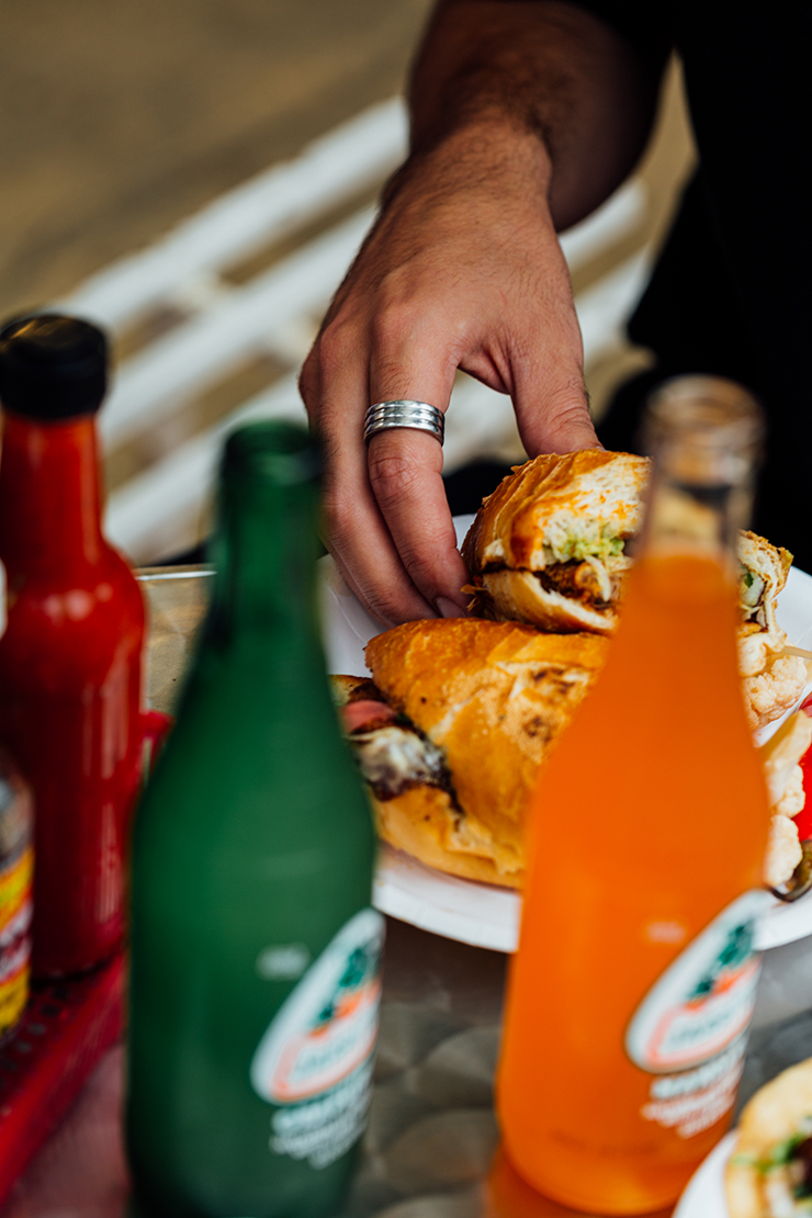 Hot sauce, Mexican soda and a torta from Frankie's stacked casually on a table.